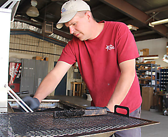 Darin Brage, service technician for North Star Energy, cleans a grill as part of a tune-up service offered by the company. There are many problems that can be encountered after a gas grill has been stored for the winter, he said.