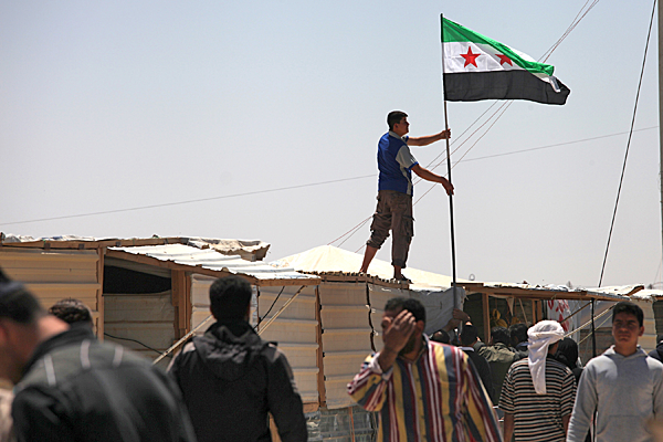 A Syrian refugee hoists the Syrian revolutionary flag over a makeshift shop, during a strike at Zaatari refugee camp, in Mafraq, Jordan.