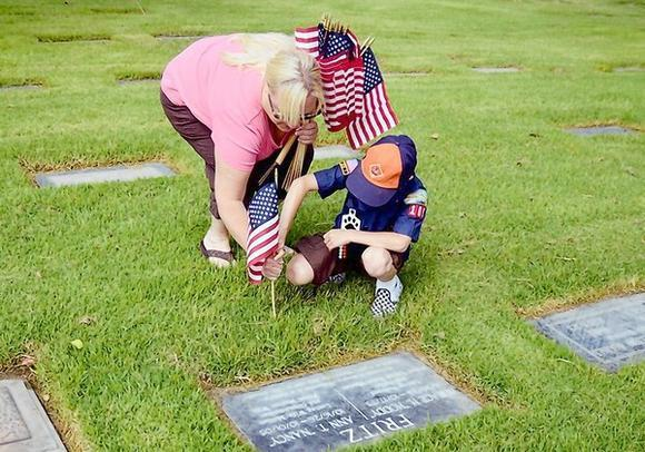 U.S. Coast Guard veteran Abby Beck, left, places a flag on the grave site of a fallen soldier with her son Levi, 7, at a Memorial Day commemoration by Costa Mesa Tiger Cub Scout Pack 108 at Pacific View Memorial Park and Mortuary in Newport Beach on Saturday.