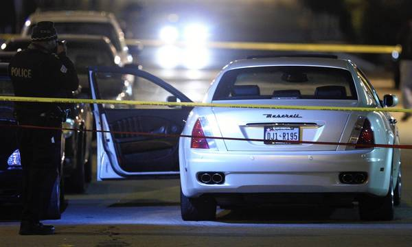 A Chicago Police officer photographs a car involved in an overnight shooting on N. North Branch Street in Chicago.