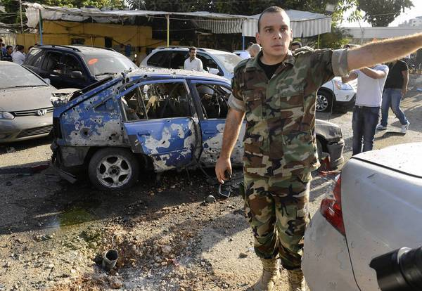 A Lebanese army officer asks journalists to step back at the scene of a rocket attack in the Beirut area.