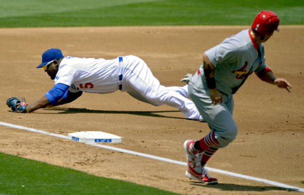 Dodgers third baseman Juan Uribe dives but can't stop a ball hit by the Cardinals' Pete Kouzma (not pictured) for a three-run double that scored, among others, Yadier Molina.