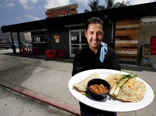 Mexicali Taco & Co. co-owner Esdras Ochoa with a plate that includes a taco made of flour tortillas.