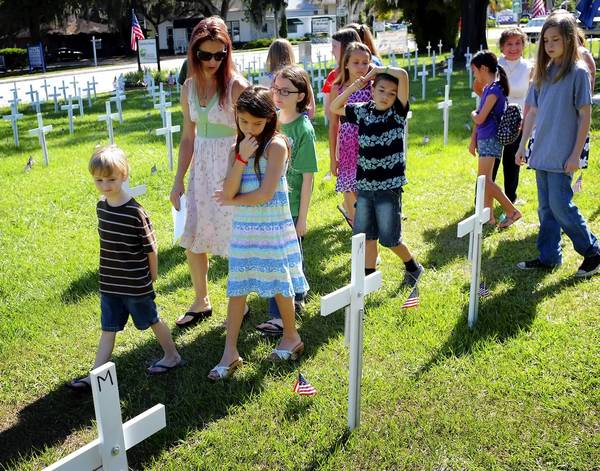 First United Methodist Church of Oviedo Sunday school teacher Kitty Rivera walks with some of her students through the hundreds of crosses honoring the Florida soldiers who have died while serving in Iraq and Afghanistan on Sunday, May 26, 2013.