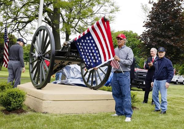 Aureliano Delatorre of the Aurora Veterans Advisory Council steadies a 45-star flag across the barrel of the 19th century cannon unveiled Sunday in Montgomery.