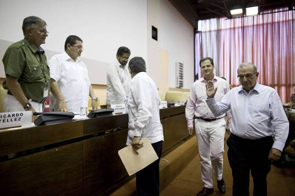 Humberto de la Calle, right, head of the Colombian government's peace negotiation team, greets FARC members, from left, Ricardo Tellez, Pablo Catatumbo and Ivan Marquez during their peace talks in Cuba.