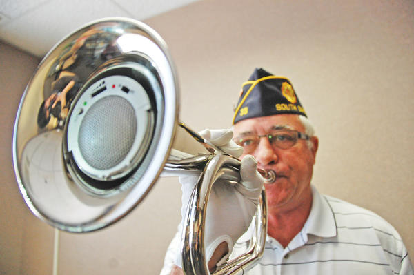Bob Wegner, commander of the Groton American Legion, demonstrates how a speaker placed inside the bugle functions during a ceremony.
