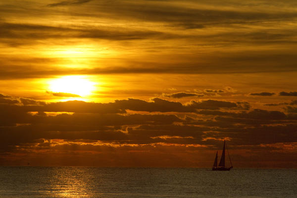 A sailboat glides across a colorful horizon off of Fort Monroe early Monday.