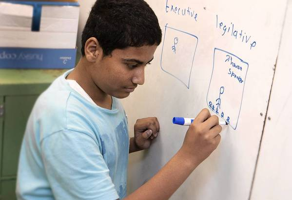 Kirtan Patel, a Lindsay Middle School eighth-grader, is getting ready to head to the Scripps National Spelling Bee. Here, he draws to reinforce the definition of a word.