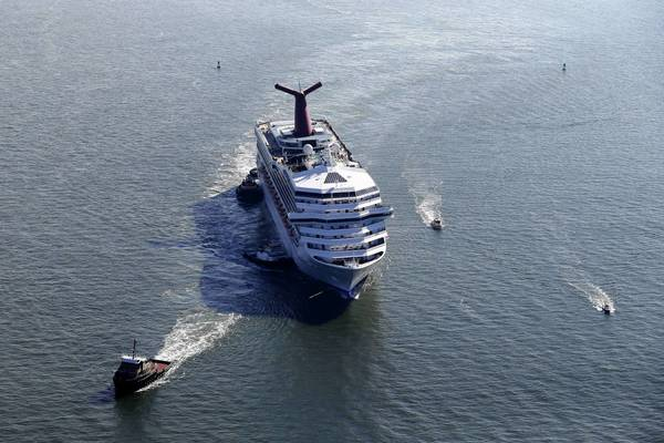 The Carnival Triumph, a cruise ship that was left powerless at sea after a fire, is towed to harbor off Mobile Bay, Ala.