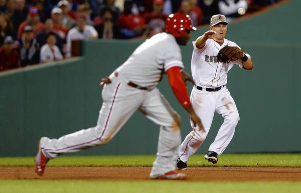 Red Sox shortstop Stephen Drew throws to second base to catch the Phillies' Ryan Howard in a run down before being tagged out in the eighth inning.