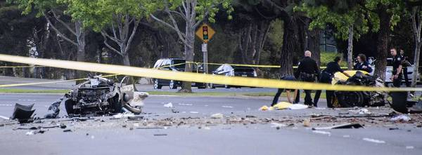 The twisted wreckage of an Infiniti litters Jamboree Road in Newport Beach after the car smashed into a tree, split apart and burst into flames. Five people were killed.