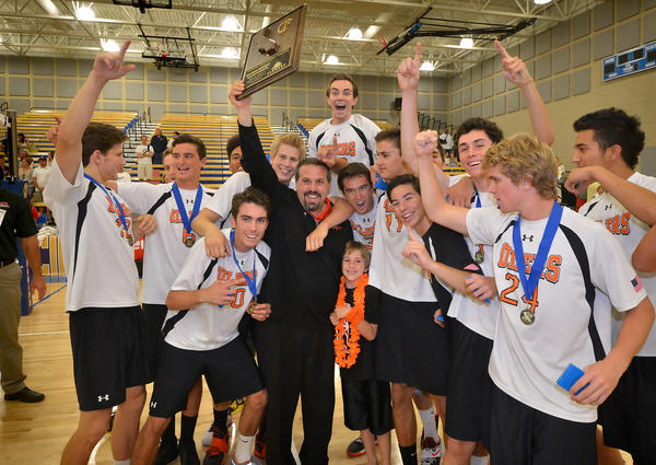 Huntington Beach boys' volleyball head coach Craig Pazanti stands next to his son Jake and his team as he holds up their first place CIF SoCal Regional State Division 1 championship plaque after defeating Loyola, 3-2, late Saturday night at Santiago Canyon College.