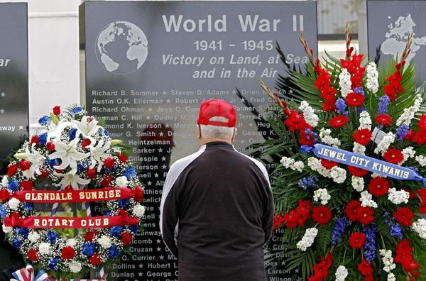 Cal Drake, 83, of Glendale, stops to look for his father's name at the World War II Memorial at City Hall in Glendale on Monday. His father, Hubert Drake, was killed while fighting in World War II.