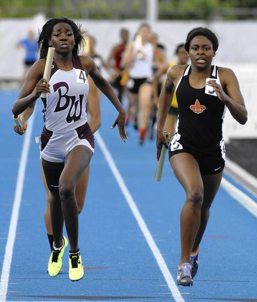 St. Charles East's Britney Williams, right, runs the final leg of the 1,600 relay during the girls state track meet earlier this month.