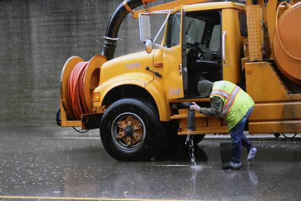 In this Tribune file photo, Illinois Department of Transportation worker clears out water from his boot after trying to decrease the water level under a Metra bridge on Waukegan Road in Glenview on April 18.