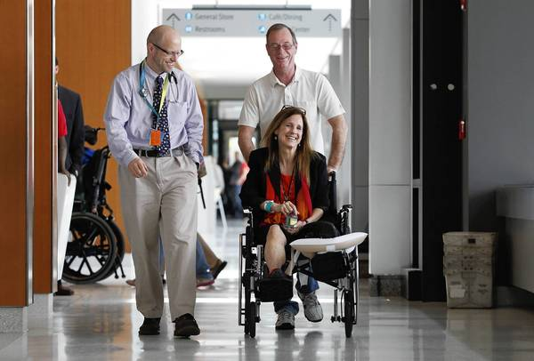 Dr. David Crandell, left, laughs with Boston Marathon victim Beth Roche as she is wheeled toward a press conference by her husband, Ken, at Spaulding Rehabilitation Hospital in Charlestown, Massachusetts. Roche will be released from Spaulding at the end of the week.