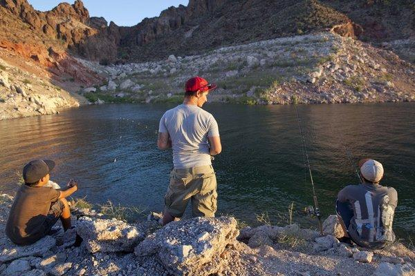 "Kids fishing at Kingman Wash wait for bass to bite at Lake Mead National Recreation Area in Arizona. A ""bathtub ring"" marking Lake Mead's highest levels is visible in the background."