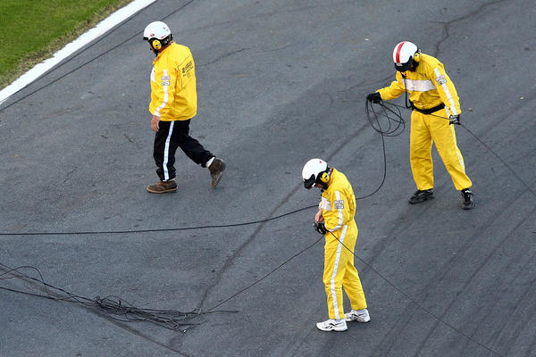 Track workers clean up cable from an aerial Fox Sports camera on the front stretch during a red flag in the NASCAR Sprint Cup Series Coca-Cola 600 at Charlotte Motor Speedway.