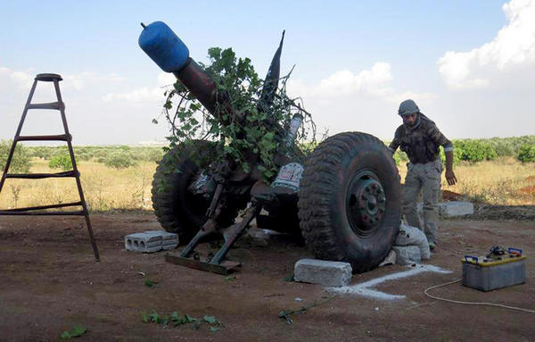 A Syrian rebel fires shells made from gas cylinders in Idlib province.