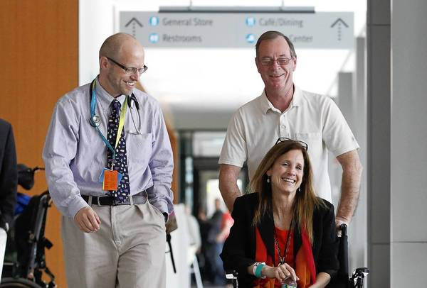 Dr. David Crandell, left, smiles as Boston Marathon victim Beth Roche is wheeled toward a news conference by her husband, Ken, at Spaulding Rehabilitation Hospital.