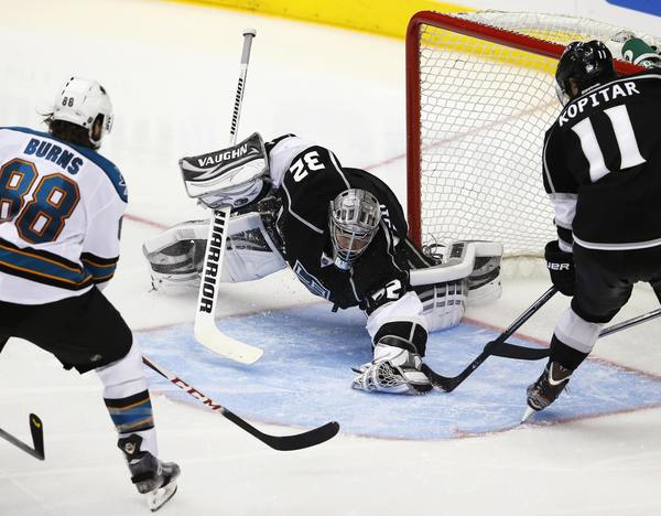 Kings goalie Jonathan Quick gets help from Anze Kopitar as he beats the Sharks' Brent Burns to the puck in the third period.
