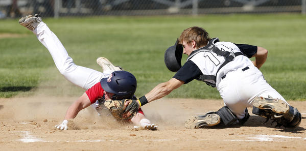 Mike Stotz of the Aberdeen Smittys, right, reaches to make the tag on Seth Bjordal of Sioux Falls West, at the plate during Tuesday's first game at Fossum Field.