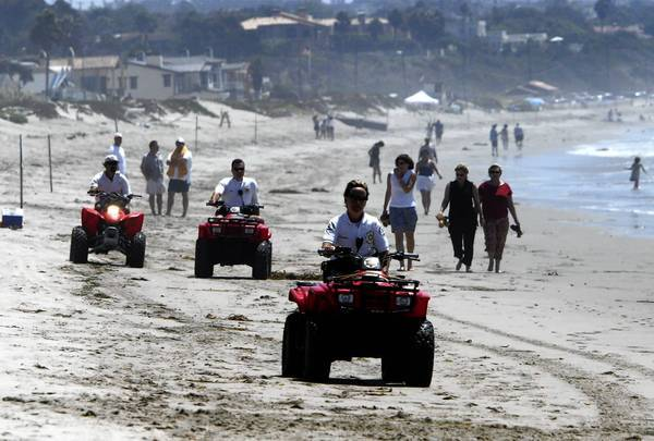 Security guards riding ATVs patrol Broad Beach. Homeowners hire the guards to keep visitors off public beaches.