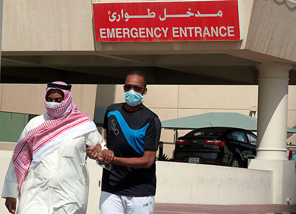 A man, wearing a surgical mask as a precautionary measure against the novel coronavirus, helps a friend who has the common flu near a hospital in Khobar city in Dammam May 23, 2013. Saudi Arabia has announced another death from the SARS-like novel coronavirus (nCoV) in its central al-Qassim region.