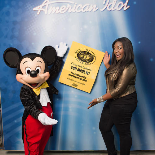 "Reigning ""American Idol"" champion Candice Glover poses with Mickey Mouse outside the American Idol Experience attraction at Disney's Hollywood Studios on May 27, 2013. Glover was at Walt Disney World to tape audio and video segments for the attraction, which features park guests as singers."