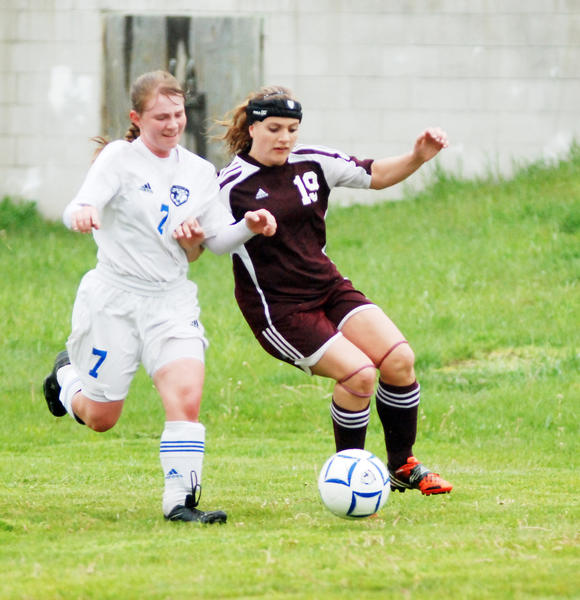 Burt Lake Northern Michigan Christian Academy defender Courtney Spears (left) and Charlevoix forward Kaitlin Hinkley battle for possession during a district match Tuesday at Burt Lake. The Radyers defeated the Eagles, 1-0.