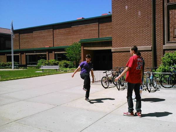 A group of students play footbag outside of Lyons Township High School on Friday. The school's prom is May 30.