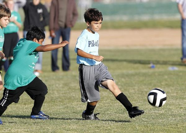 Newport Heights' William Haide, right, kicks the ball during a Daily Pilot Cup boys' third- and fourth-grade silver division game against Lincoln on Tuesday.