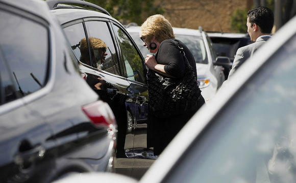 A customer shops for cars at a Ford dealership in Colma, Calif., in March.