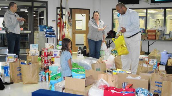 From left, Adam Miklaszewski, Ellie Pena, Erica Miklaszewski, and Ruben Pena survey items donated for tornado relief.