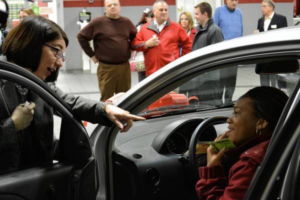 Naperville resident and single mother Nikita Hawkins (behind the wheel) was given a used car last December, by Naperville CARES and Continental Motors. At left is Continental Toyota dealer Cheryl Nelson.