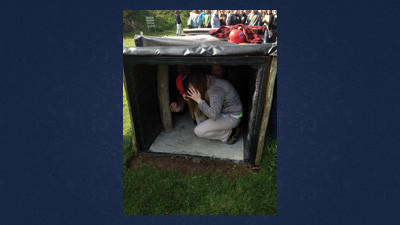 Bishop Carroll student Katie Bender goes through the squeeze box at the Quecreek Mine memorial museum. The box is meant to simulate the space miners would have to walk and move around.