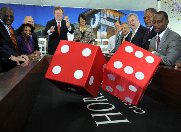 Caesars Entertainment Chairman, President and CEO Gary Loveman and Baltimore Mayor Stephanie Rawlings-Blake throw ceremonial dice at the groundbreaking event for Horseshoe Casino Baltimore near M&T Bank Stadium.