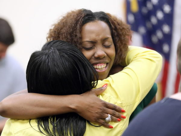 Domestic violence survivor Versanette Blackman shares a hug after the city on Wednesday announced its first new shelter in more than a decade.