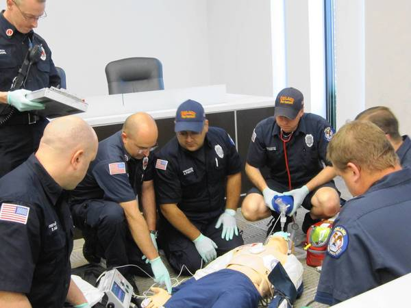 Orland Fire Protection District firefighters demonstrate a new high-performance CPR response at a board of trustees meeting May 28.