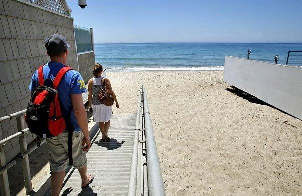 Tourists access Carbon Beach in Malibu through a public accessway alongside David Geffen's home on Monday. Malibu residents say beachgoers often trash the areas in front of their homes.