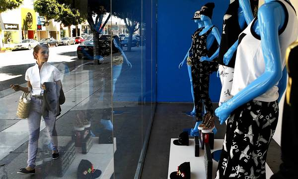 Elizabeth Ashworth passes by a storefront on Robertson Boulevard in Los Angeles on her way to work. Rents for retail properties are rising again.