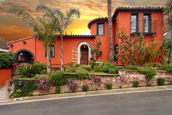 The updated Spanish-style house features a red tile roof, arches and a front balcony.