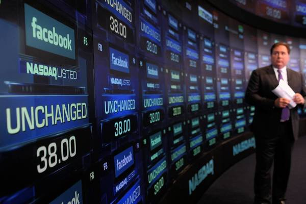 Nasdaq's computer systems had a design flaw that failed to properly match orders to buy and sell Facebook shares on their May 18, 2012, public debut, causing havoc in how the stock traded. Above, a reporter waits for Facebook stock to start trading on May 18.