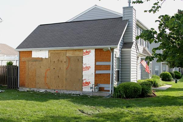 A large section of a home on Timberneck Lane in Newport News is boarded up after a car careened into it Monday. A man who was in the home died after the crash, and the driver has been charged in the incident.