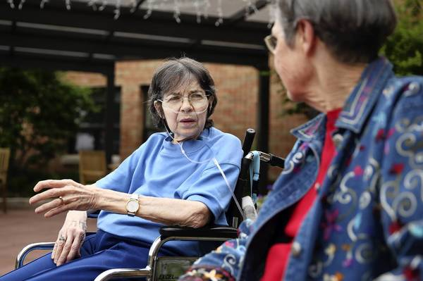 Helen Smith, left, visits with her sister, Carol Kilduff, at a nursing home in Naperville. Kilduff had trouble canceling her sister's Comcast service for her.