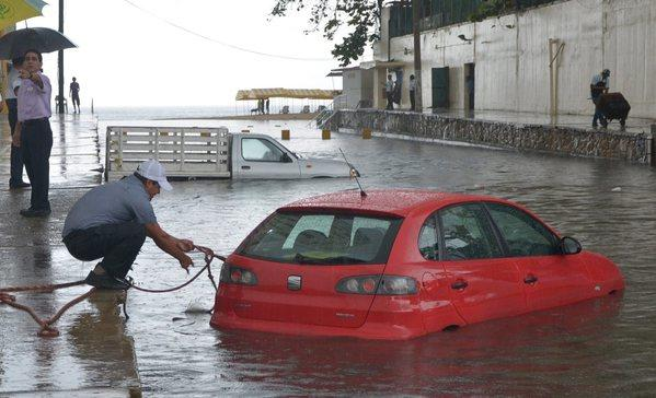 A man tries to rescue his stranded vehicle in the Pacific port of Acapulco, in Guerrero, Mexico