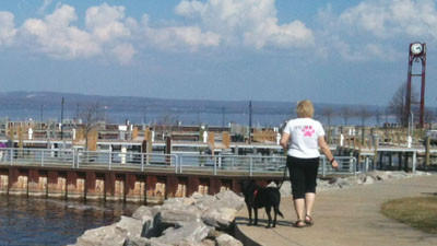 Marcie Wolf, owner of the new Wait.Sit.Stay dog walking service, walks her dog along the Petoskey waterfront.