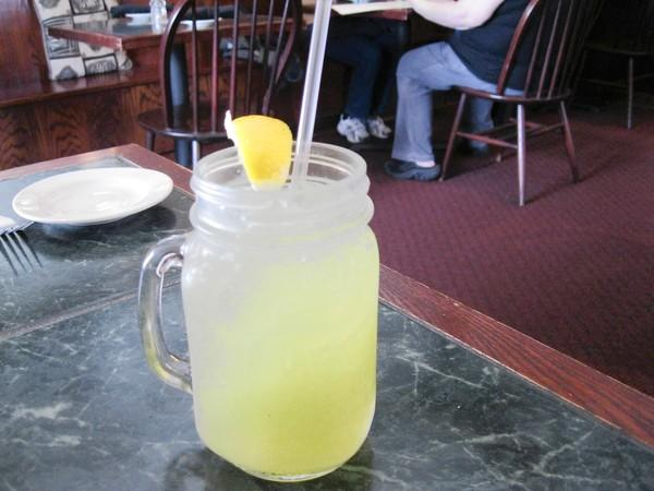 Lemonade, jazzed up with basil and served in mason jar with a handle and a straw.