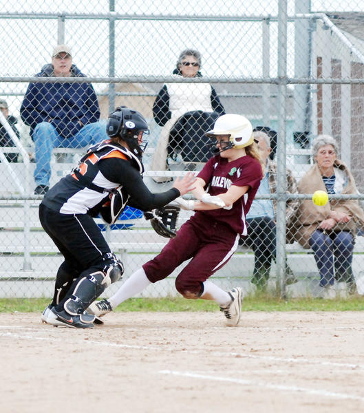 Charlevoixs Kelsey Pischner (right) scores the Rayders sixth run in the fourth inning against Elk Rapids during a pre-district game Wednesday at Charlevoix High School.